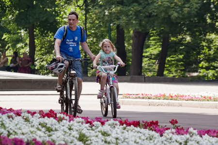 bicycling: KHARKIV, UKRAINE - JUNE 25, 2016: Unidentified father and daughter riding on bicycles in the park. Bicycling is becoming popular lately in Ukraine Editorial