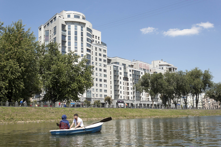 residents: KHARKIV, UKRAINE - JUNE 30, 2014: Boating on the Kharkiv river near modern high-rise - one of the favorite pastimes of residents and visitors Editorial