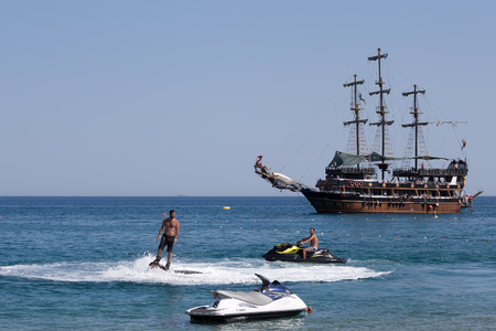 personal watercraft: CAMYUVA, KEMER, TURKEY - JULY 16, 2015: On the coast of Turkey along with the traditional personal watercraft are becoming popular flyboard and yachting stylized pirate schooner Editorial