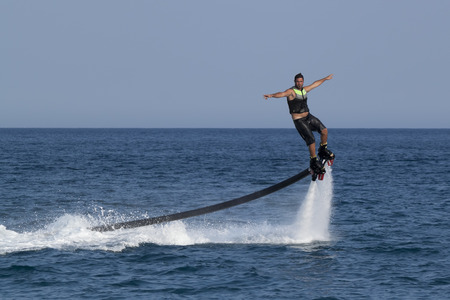increasingly: CAMYUVA, KEMER, TURKEY - JULY 12, 2015: Unidentified Turkish man hovered above the water. Extreme water sports are increasingly popular on the beaches of Turkey