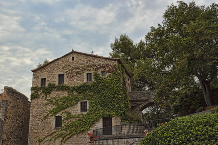 twined: GIRONA, SPAIN - JULY 17, 2013: In the historic center of Girona. Old house, twined with green leaves. Well preserved since the Middle Ages the historic core of the city attracts a significant number of tourists