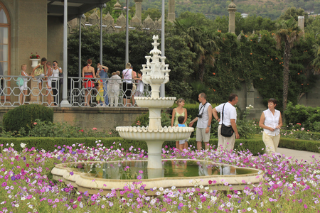 ALUPKA, CRIMEA, UKRAINE - AUGUST 11, 2010: A flower bed with a fountain on the south terrace of the Vorontsov Palace in the Crimea. There were always a lot of tourists