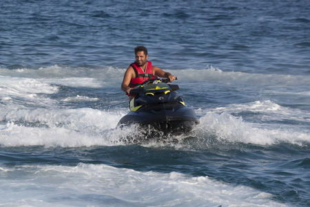 turkish man: CAMYUVA, KEMER, TURKEY - JULY 16, 2015: Unidentified Turkish man glides over the waves of the Mediterranean Sea on Jet Ski. Extreme water sports are increasingly popular on the beaches of Turkey