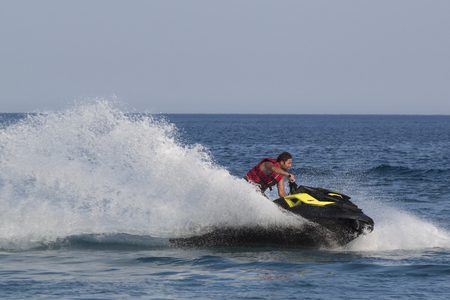 personal watercraft: CAMYUVA, KEMER, TURKEY - JULY 16, 2015: Unidentified Turkish man turns sharply over the waves of the Mediterranean Sea on Jet Ski. Extreme water sports are increasingly popular on the beaches of Turkey Editorial