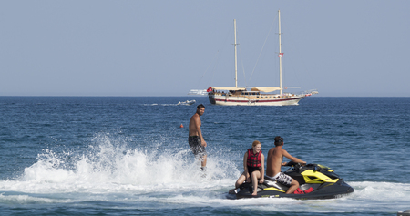 jet skier: CAMYUVA, KEMER, TURKEY - JULY 16, 2015: Unidentified Turkish man communicates with the jet ski driver. It is the interaction with the jet ski driver must be flyboarders