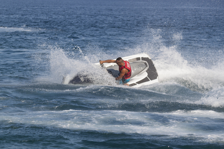 sharply: CAMYUVA, KEMER, TURKEY - JULY 16, 2015: Unidentified Turkish man turns sharply over the waves of the Mediterranean Sea on Jet Ski. Extreme water sports are increasingly popular on the beaches of Turkey Editorial