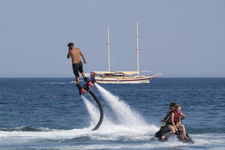 increasingly: CAMYUVA, KEMER, TURKEY - JULY 16, 2015: Unidentified Turkish man hovered above the water. Extreme water sports are increasingly popular on the beaches of Turkey