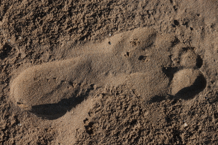 Trace a bare foot on the sand