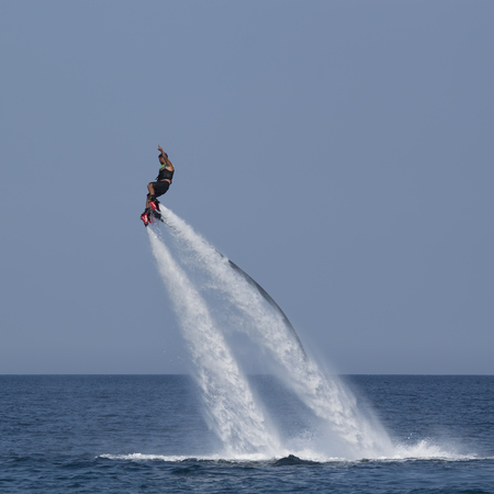 turkish man: CAMYUVA, KEMER, TURKEY - JULY 12, 2015: Unidentified Turkish man hovered above the water. Extreme water sports are increasingly popular on the beaches of Turkey