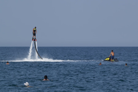 propulsion: CAMYUVA, KEMER, TURKEY - JULY 12, 2015: Unidentified Turkish man hovered above the water. Extreme water sports are increasingly popular on the beaches of Turkey