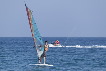 turkish man: CAMYUVA, KEMER, TURKEY - JULY 11, 2015: Unidentified Turkish man glides over the waves of the Mediterranean Sea windsurfing. Extreme water sports are increasingly popular on the beaches of Turkey