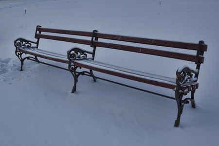 drifts: A lonely bench covered with snow drifts