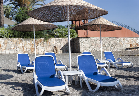 Empty deckchairs and umbrellas with a thatched roof on the beach in Turkey. Camyuva, Kemer Stock Photo