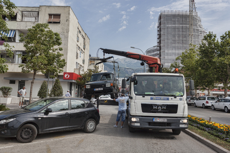 BUDVA, MONTENEGRO - JUNE 26, 2017: A large number of cars in Budva (Montenegro) in the tourist season. For the slightest violation of parking rules, the car is taken to the penalty area by an evacuator Editorial