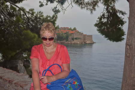 A mature woman on the background of the island of Sveti Stefan. Smiling, looking over his sunglasses