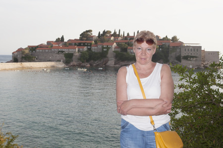 A mature woman on the background of the island of Sveti Stefan. Smiling Stock Photo
