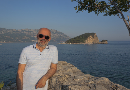 A mature man on the background of the island of Sveti Nicola. Smiling, looking through his sunglasses