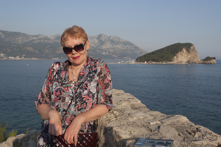 A mature woman on the background of the island of Sveti Nicola. Smiling, looking through his sunglasses