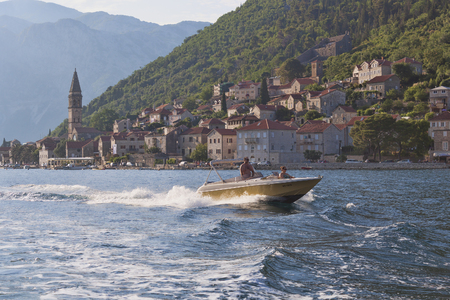 PERAST, MONTENEGRO - JUNE 27, 2017: Unknown man and woman travel by boat along the Boka-Kotor Gulf. Éditoriale
