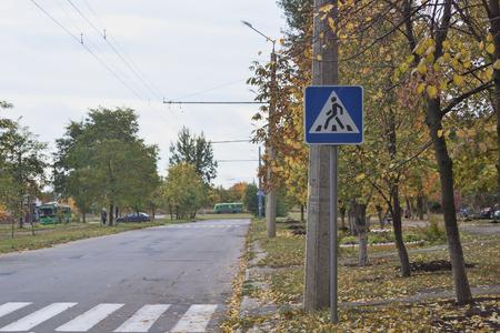 KHARKIV, UKRAINE - OCTOBER 15, 2017: Road with sign Pedestrian crossing. Near autumn trees