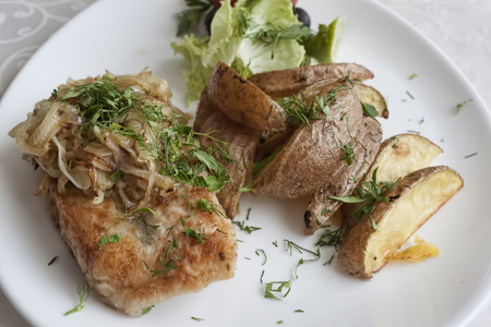 Fish served with passionated onion and herbs with baked potatoes and lettuce