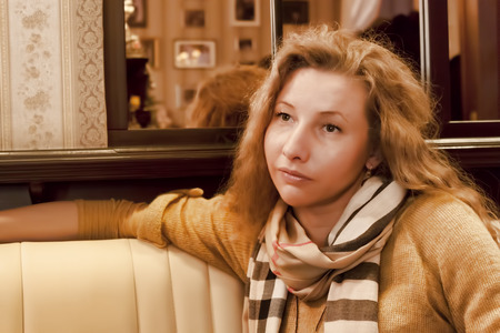 Young woman with her hair and scarf around her neck on the couch