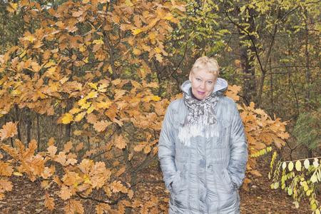 Mature woman near the autumn oak. Woman in a long gray raincoat Stock Photo