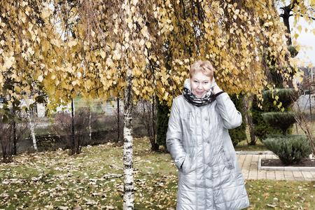 Mature woman near the autumn birch. Woman in a long gray raincoat