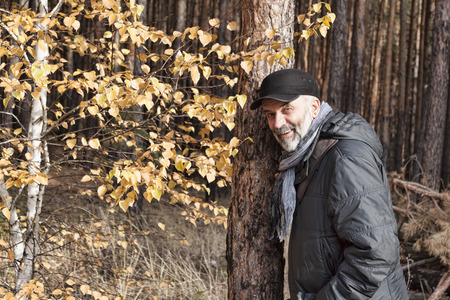 A mature man with a beard in a baseball cap, a jacket with a scarf around his neck in the autumn forest