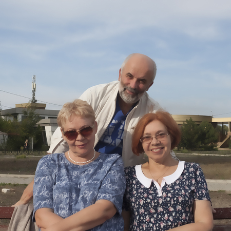 Two mature women sit on a bench, behind them a man stand. Warm September