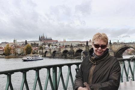A mature woman in sunglasses on the Vltava embankment in Prague