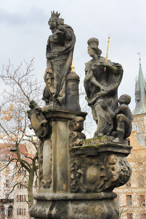 PRAGUE, CZECH REPUBLIC - NOVEMBER 5, 2012: Sculptural composition on the Charles Bridge: St. Margaret, Varvara and Elizabeth. On the pedestal is the inscription: Pray for us now and at the hour of death Editorial