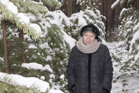 Mature woman in a snowy forest. Behind the young pines are covered with first snow