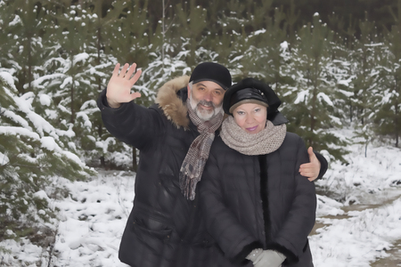 Mature couple in a snowy forest. Behind the young pines are covered with first snow