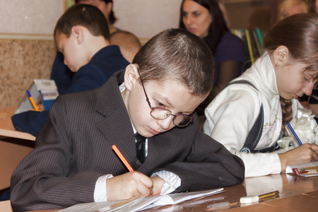 SLOVIANSK, UKRAINE - NOVEMBER 17, 2011: An unknown junior student at a desk writes something in a notebook at a lesson in one of the schools in Sloviansk
