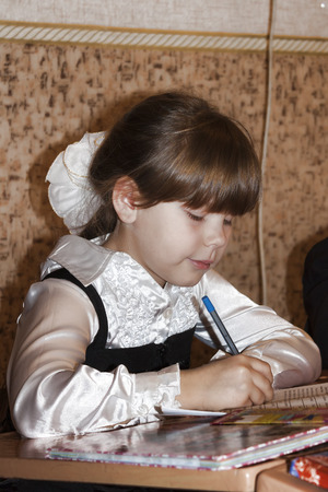 SLOVIANSK, UKRAINE - NOVEMBER 17, 2011: An unknown junior girl at a desk writes something in a notebook at a lesson in one of the schools in Sloviansk Editorial