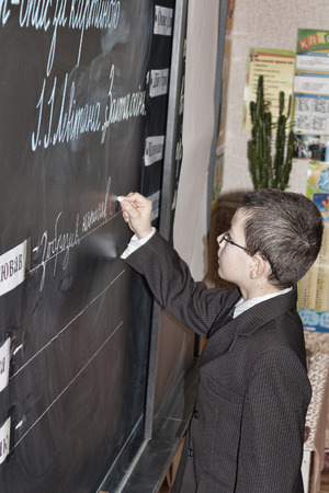SLOVIANSK, UKRAINE - NOVEMBER 17, 2011: An unknown pupil of junior classes at the blackboard writes something in chalk at a lesson in one of the schools of Sloviansk