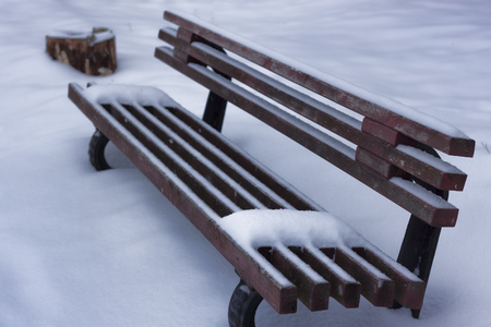A lonely bench covered with snow drifts