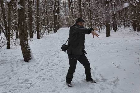 A mature man plays snowballs in the winter forest. Stock Photo