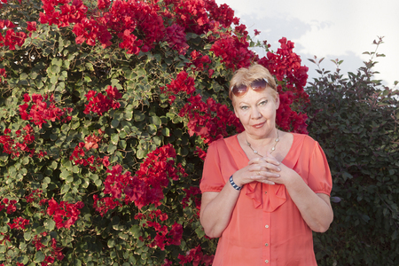 A woman of mature years in red dress among the January flowers of Sharm El Sheikh