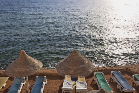 Empty chaise lounges and awnings on the beach. Coast of the Red Sea.