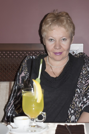 A mature woman in a cafe. On the table, ginger tea Stock Photo