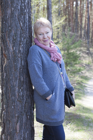 A mature woman in the forest. Half-turned back to the tree