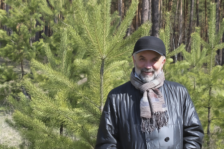 A man of mature age near young pine trees in a coniferous forestÑŽ A man in a jacket, with a scarf and a baseball cap