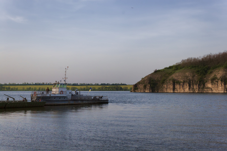 USTYA, UKRAINE - MAY 3, 2013: The River Smotrich flows into the Dniester, near the village of Ustya near Kamenets-Podilsky. A small ferry running between shores Editorial