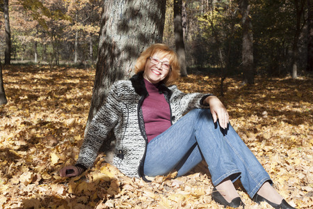 Portrait of a mature woman in an autumn forest, sitting on yellow leaves, leaning on a tree