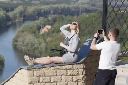 SVIATOHIRSK, UKRAINE - APRIL 30, 2018: A young couple is photographed on the observation deck of the Nikolayevskaya church against the background of the Seversky Donets River