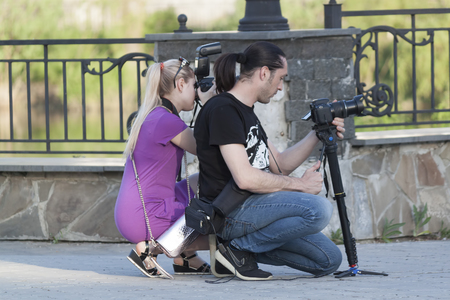 SVIATOHIRSK, UKRAINE - MAY 6, 2018: Unknown photographers on the Sviatohirsk embankment, a favorite place for wedding couples Editorial