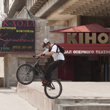 KHARKIV, UKRAINE - JUNE 13, 2011: An unknown young man riding a bicycle on the square in front of the Kharkiv Opera House, shows extreme stunts