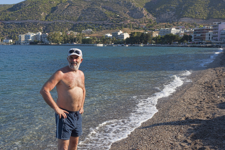 A man of mature age on the beach in Loutraki, Greece Stock Photo
